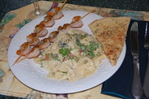Farfalle with Bacon, Peas and Sage plated with grilled shrimp and garlic bread